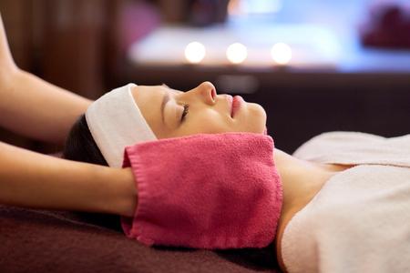 mensen, schoonheid, levensstijl en ontspanningsconcept - mooie jonge vrouw die met gesloten ogen liggen en gezichtsmassage met badstofhandschoenen hebben bij kuuroord