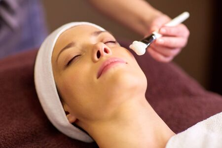 face mask: people, beauty, cosmetology and treatment concept - close up of beautiful young woman lying with closed eyes and cosmetologist applying facial mask by brush at spa