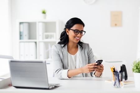 Business, Technologie, Kommunikation und Menschen Konzept - glücklich lächelnde Geschäftsfrau mit Smartphone und Laptop im Büro