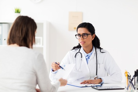 doctor with clipboard and woman at hospital