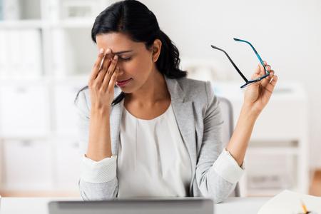 Zakenvrouw wrijven moe ogen op kantoor Stockfoto