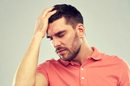 unhappy people: people, crisis, emotions and stress concept - unhappy man suffering from head ache over gray background