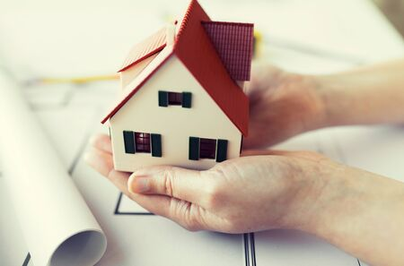 architect drawing: architecture, building, construction, real estate and people concept - close up of architect hands holding living house model above blueprint on table Stock Photo