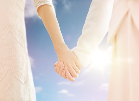 matrimonio feliz: people, homosexuality, same-sex marriage and love concept - close up of happy married lesbian couple holding hands over sky and sun background