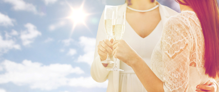 matrimonio feliz: people, homosexuality, same-sex marriage, celebration and love concept - close up of happy married lesbian couple holding and clinking champagne glasses over sky and sun background Foto de archivo