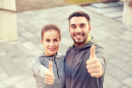 fitness, sport, people and gesture concept - smiling couple outdoors showing thumbs up on city street stairs Stock Photo