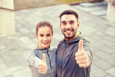 Fitness, sport, persone e concetto di gesto - sorridente coppia all'aperto mostrando i pollici su scale di strada della città Archivio Fotografico - 76188684