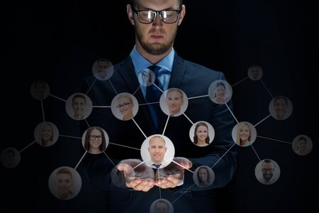 network people: business, virtual reality, future technology, cyberspace and people - businessman with network contacts over black background Stock Photo