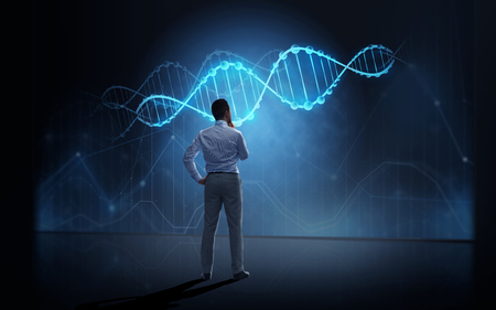 business, people, technology and science concept - businessman looking at virtual dna molecule projection over dark background from back Stock Photo