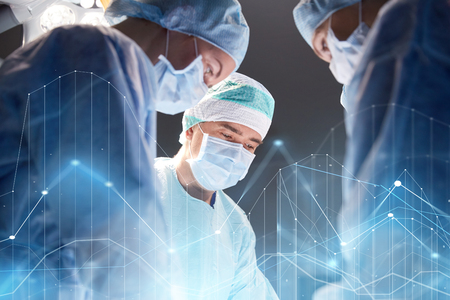 surgery, healthcare, medicine and people concept - group of surgeons at operation in operating room at hospital with virtual diagram projection Stock Photo