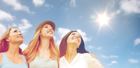 summer holidays, friendship and people concept - group of happy smiling women or friends over sky and sun background