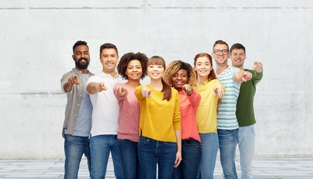 diversity, choice, ethnicity and people concept - international group of happy smiling men and women pointing finger on you over stone wall background