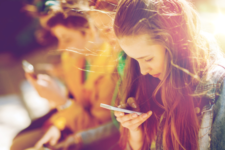 technology, internet addiction and people concept - happy teenage friends with smartphones outdoors