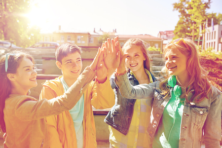 education, high school, friendship, gesture and people concept - group of happy teenage students or friends making high five outdoors Stock Photo