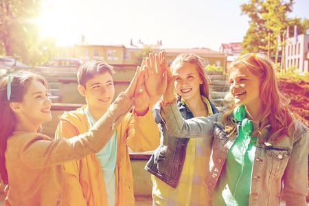 l'éducation, l'école secondaire, l'amitié, le geste et les gens concept - groupe heureux étudiants ou amis adolescents faisant cinq élevés en plein air