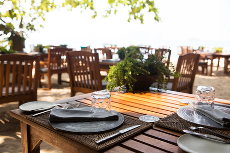 leisure, travel and tourism concept - served table at open-air restaurant on beach