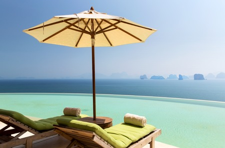 daybed: infinity pool with parasol and sun beds at ocean