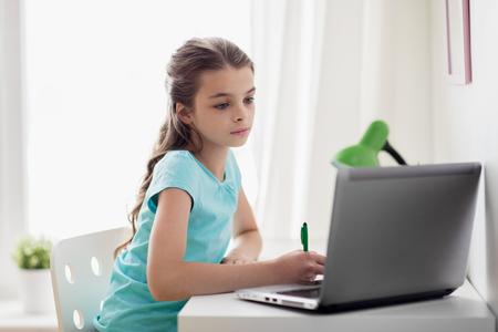 meisje met een laptop schriftelijk aan notebook thuis