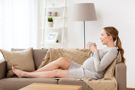 happy pregnant woman with cup drinking tea at home photo