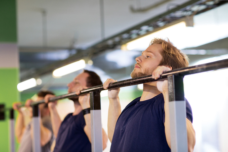 group of young men doing pull-ups in gym Stock Photo