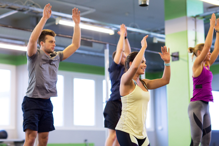 group of happy friends exercising in gym Stock Photo