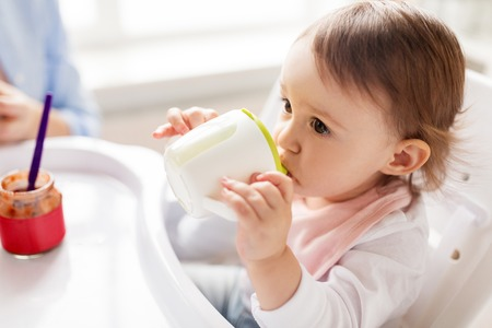 baby drinking from spout cup in highchair at home Banco de Imagens