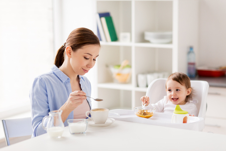 happy mother and baby having breakfast at home Stock Photo
