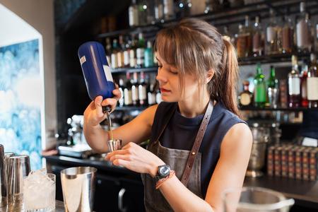 barmaid with shaker preparing cocktail at bar 版權商用圖片