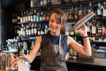 barmaid met shaker bereiden cocktail bij staaf