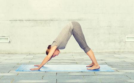 woman making yoga dog pose on mat