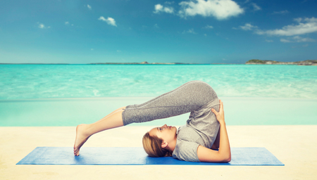 woman making yoga in plow pose on mat Stock Photo - 76359242