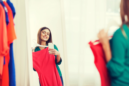woman with smartphone taking mirror selfie at home Stock Photo - 76357560