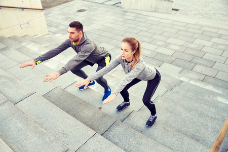 couple doing squats on city street stairs Stock Photo
