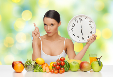 woman with food and big clock sitting at table