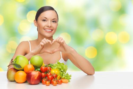 comidas saludables: mujer con frutas y verduras que muestra el corazón
