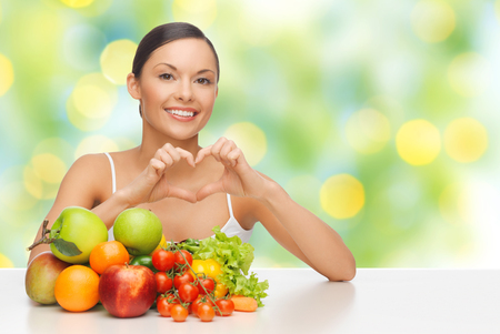 healthy foods: woman with fruits and vegetables showing heart