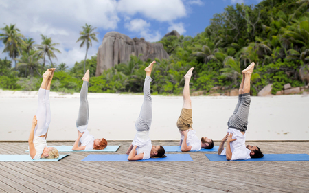 people making yoga in shoulderstand pose on mat Stock Photo - 76358441
