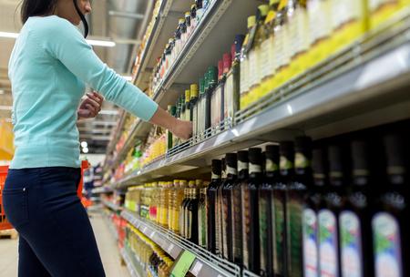 여자 슈퍼마켓이나 식료품 가게에서 올리브 오일을 선택합니다.