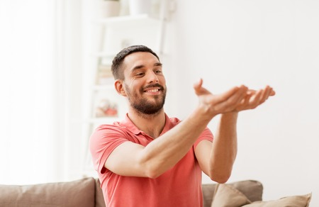 happy man holding something imaginary at home