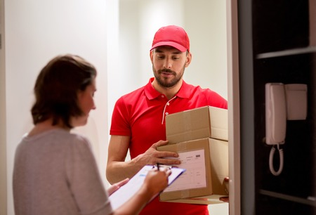 addressee: deliveryman and customer with parcel boxes at home Stock Photo