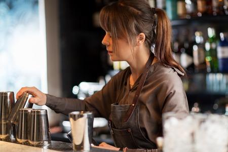 barmaid with shakers preparing cocktail at bar 版權商用圖片