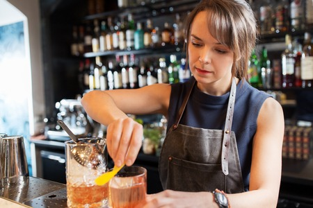 barmaid with glass and jug preparing cocktail Stock Photo