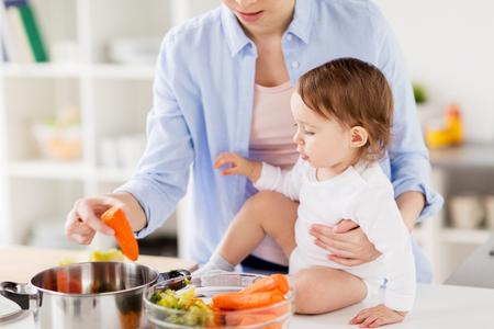 mujer sola: Feliz madre y el bebé para cocinar verduras en el hogar