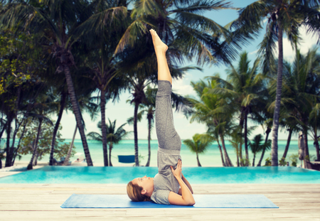 woman making yoga in shoulderstand pose on mat Stock Photo - 76687253