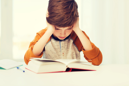 student boy reading book or textbook at home Stock Photo