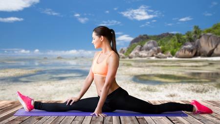 smiling woman doing splits on mat over beach