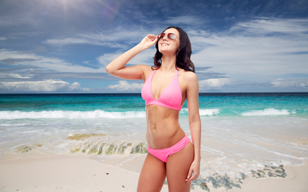 happy woman in sunglasses and bikini on beach photo