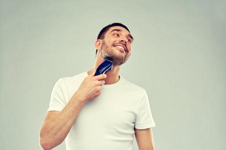 Lachende man scheer baard met trimmer over grijs Stockfoto