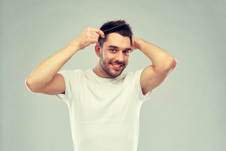happy man brushing hair with comb over gray