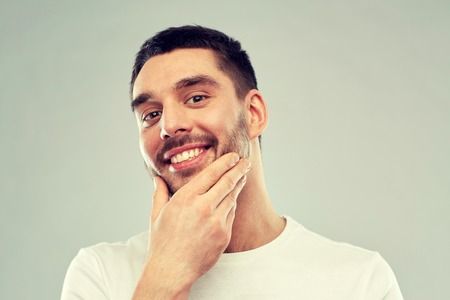 happy young man touching his face or beard Stock Photo